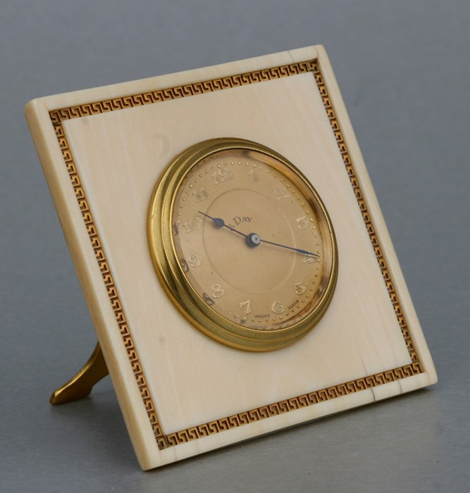 An early 20th century ivory framed strut clock, the dial with Arabic numerals within a yellow