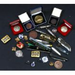 A quantity of whistles, commemorative coins, medallions, fountain pens and other items.