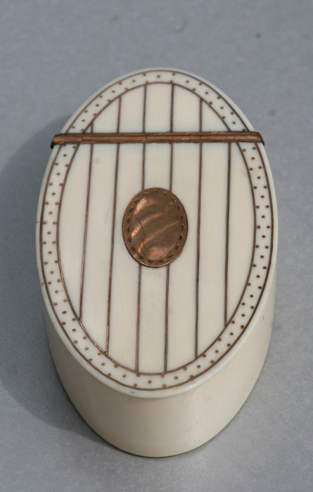 A Georgian ivory oval snuff box with yellow metal decoration and yellow metal oval blank cartouche