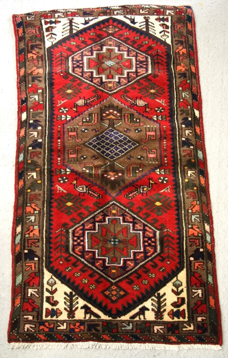 A Persian Hamadan hand knotted woollen rug with stylised design within borders, on a red ground, 163