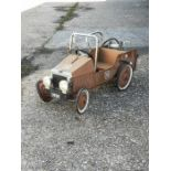 A vintage style tin plate pedal car fie engine, requiring restoration, approx 89cms (35ins) long.
