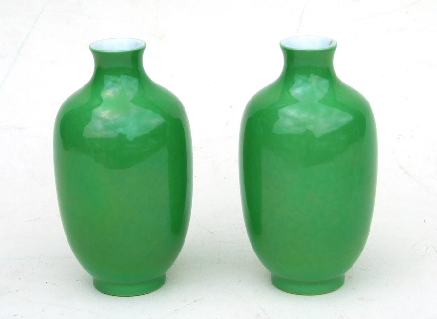 A pair of Chinese green monochrome vases with blue seal mark to the underside, 16cms (6.25ins)