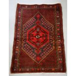 A Persian Hamadan woollen hand knotted rug with central gul within borders, 96 by 140 37.5 by