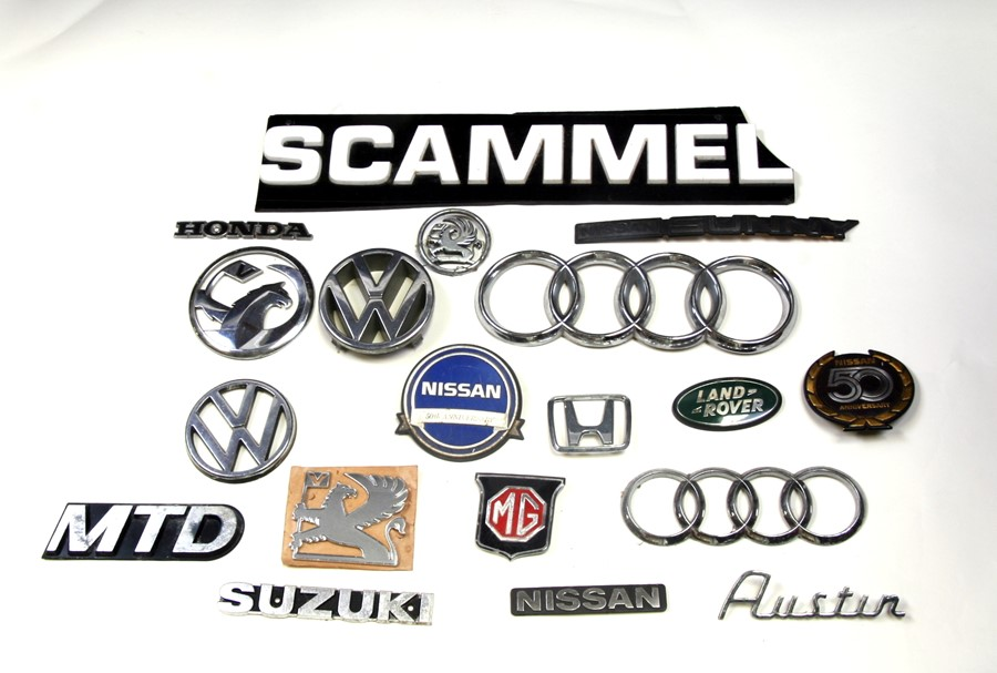 A large quantity of various marque bonnet insignias for various models including Volkswagen, Nissan,