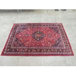 A Persian Tabriz rug with central medallion within foliate scrolls on a red ground, 210 by 305cms (