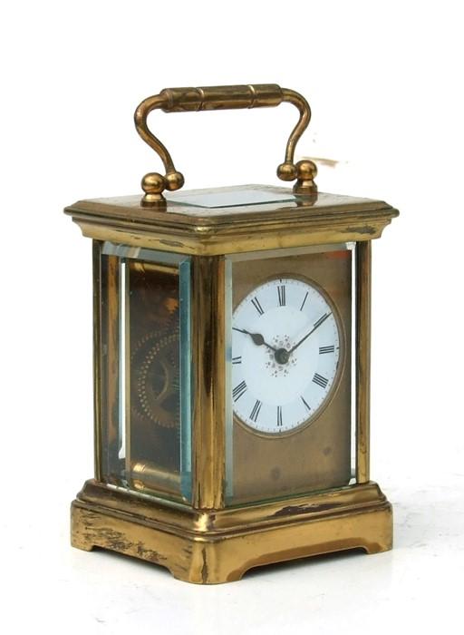 A miniature four-pillar gilt brass carriage clock, the white enamel dial with Roman numerals,