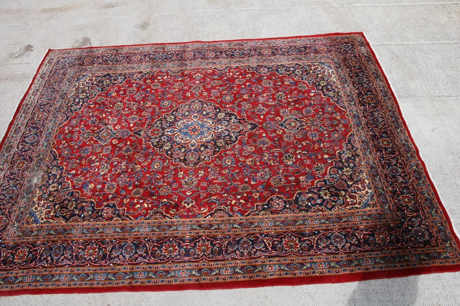 A Persian carpet with central floral medallion on a red ground within a multi floral border, 390 - Image 2 of 5