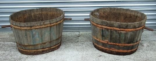 A pair of oval coopered barrels with handles, 69cms (27ins) diameter excluding handles (2).
