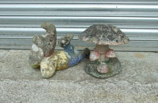 A painted stoneware garden gnome, 34cms (13.5ins) long; together with a stoneware toadstool group,