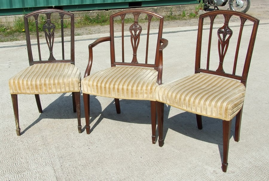 A pair of mahogany chairs with over stuffed seats on square tapering legs with spade feet;