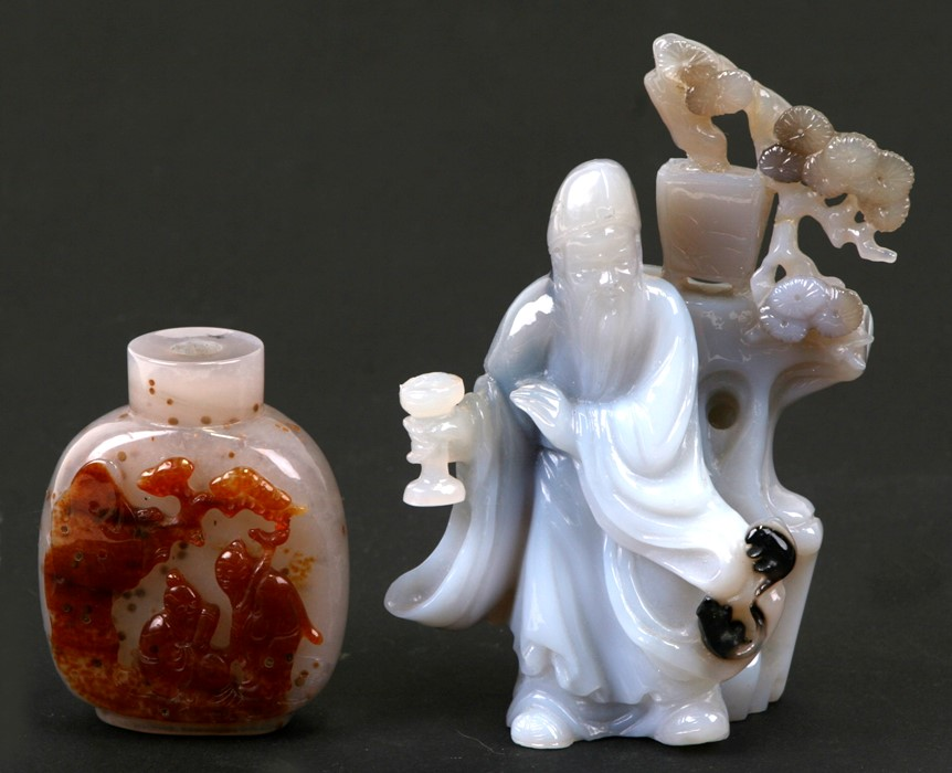 A Chinese carved agate figure depicting a robed man standing beside a tree, on a hardwood stand,