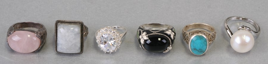 Six ornate silver gem set rings including turquoise and rose quartz.