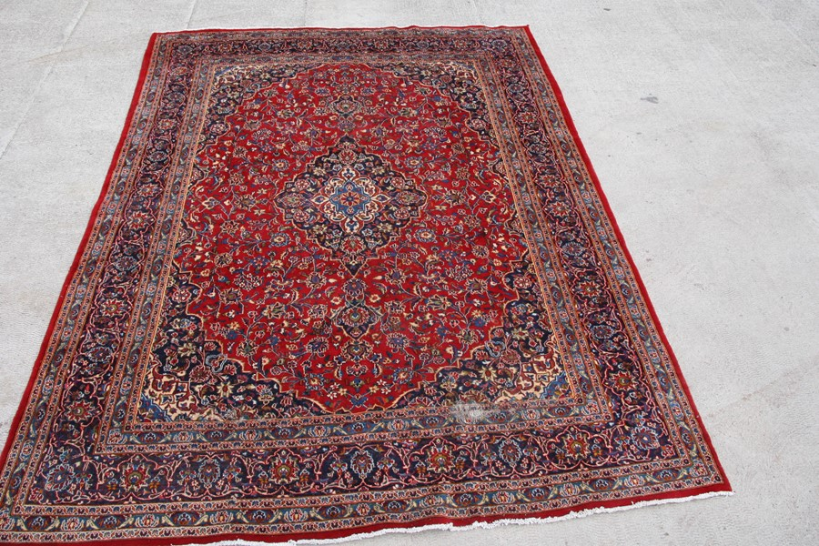A Persian carpet with central floral medallion on a red ground within a multi floral border, 390