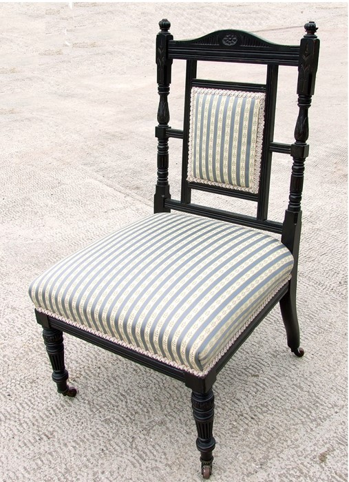 In the manner of Godwin, a Victorian ebonised nursing chair with upholstered seat, on turned front