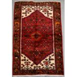 A Persian Hamadan hand knotted woollen rug with stylised central medallion within borders, 144 by