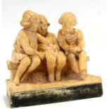 An early 20th century plaster group depicting three children seated on a bench, 30cms (12ins)
