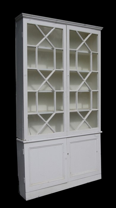 A pair of painted pine bookcases on cupboards, the pair of glazed doors enclosing a shelved interior