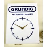 An original GRUNDIG authorised dealer electric wall clock, 30cm (12 ins) wide