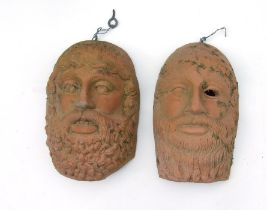 A pair of terracotta Grecian style wall masks in the form of bearded men, 22cms (8.75ins) high) (