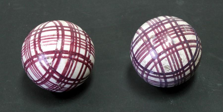 A pair of 19th century Scottish pottery carpet bowls with purple plaid decoration, 7.5cms (3ins)