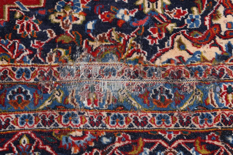 A Persian carpet with central floral medallion on a red ground within a multi floral border, 390 - Image 3 of 5