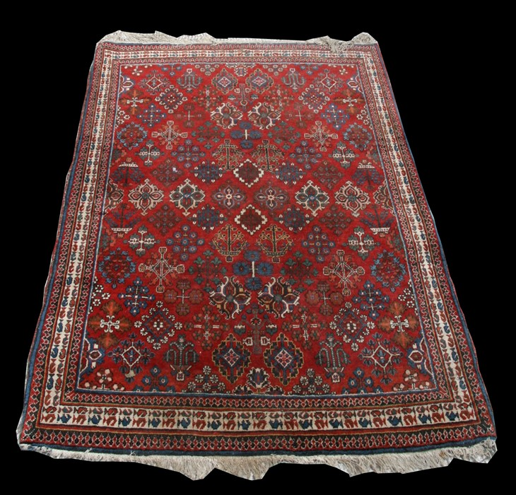 A Joshegan Persian rug with repeated design on a red ground, 153 by 107cms (60 by 42ins).