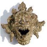 A Tibetan bronze mask incense burner, 11cm (4.25ins) long.