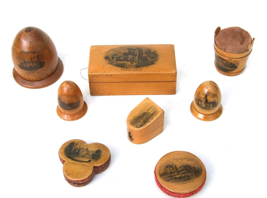 A collection of Victorian sewing related Mauchline ware to include pin cushions and thimble cases.