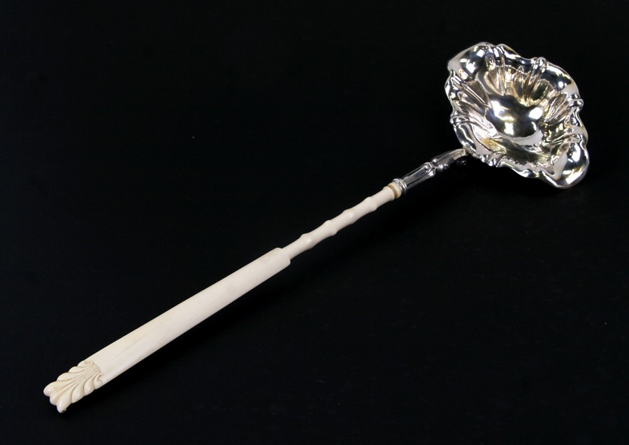 A large long ivory handled un-hallmarked silver toddy ladle, 45cms (17.75ins) long.