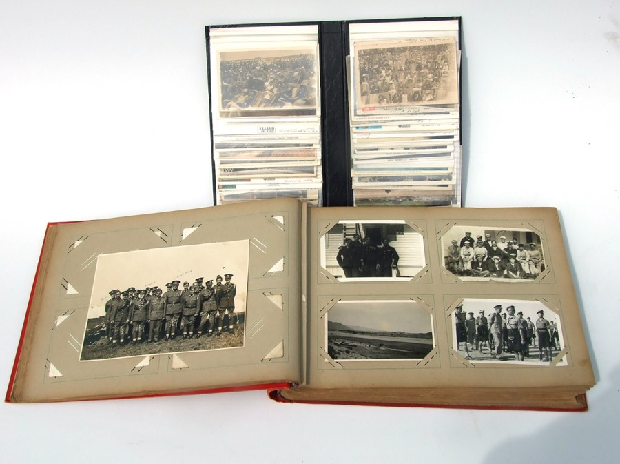 Approximately 200 early to mid 20th century Military postcards and photographs contained in a red