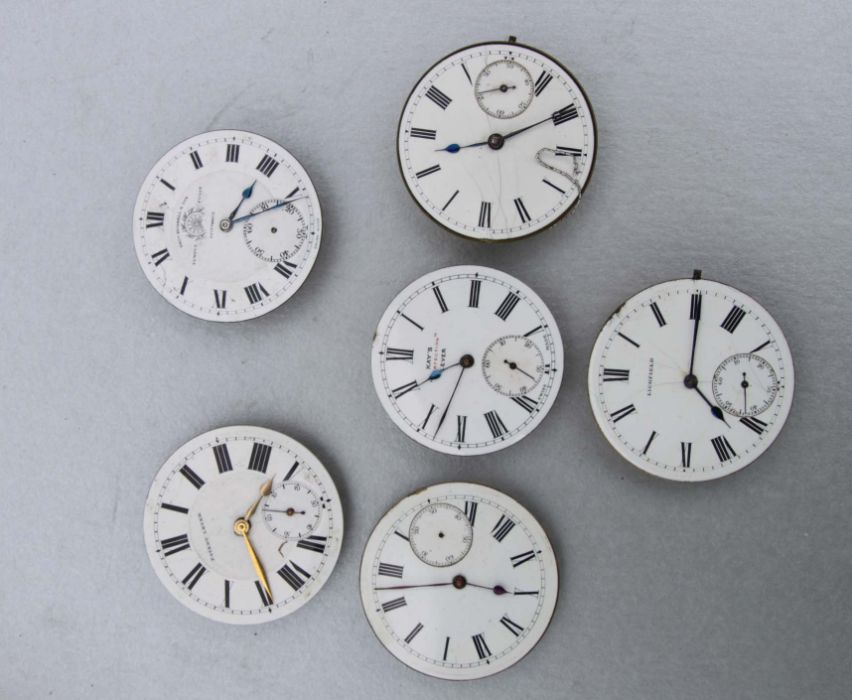 A group of pocket watch dials and movements.