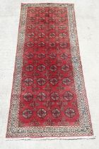 A Persian Turkoman hand knotted woollen runner with repeated rows of guls within geometric