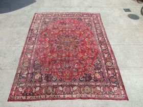 A Persian Mashad woollen hand knotted carpet with central foliate gul within foliate borders, on a