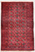 A Persian Balouch rug with repeat design on a red ground, 202 by 115cms.