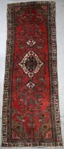 A Persian Hamadan hand knotted woollen runner with central motif within a stylised border on a red