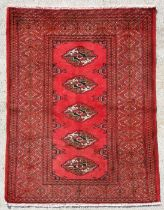 A Persian Turkoman hand knotted rug with five central guls within stylised borders, on a red ground,