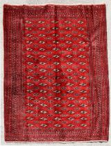 A Persian Turkoman rug with repeat design on a red ground, 180 by 130cms.