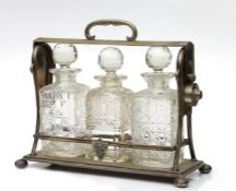 A silver plated three-bottle tantalus, 30cms high.Condition ReportSilver plate is worn and central