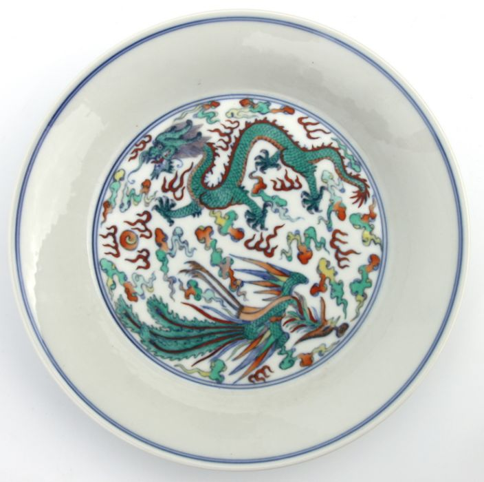 A Chinese Ducai shallow dish decorated with a dragon and phoenix chasing a flaming pearl amongst