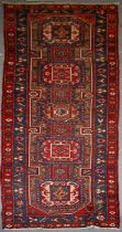 A Persian Azari hand knotted woollen runner with five stylised guls within floral borders, on a blue