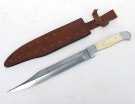 A large Bowie Knife with bone handle in its leather scabbard. Blade length 26cms (10.25ins) with