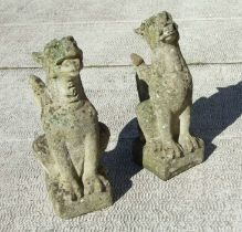A pair of well weathered reconstituted stone griffins on plinth bases, each approx 68cms high (2).