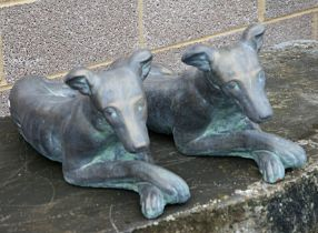 A pair of bronzed recumbent greyhounds, each approx 60cms long (2).
