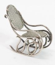 A miniature rocking chair in unmarked white metal,