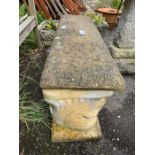 A reconstituted stone bench with decorative carvin
