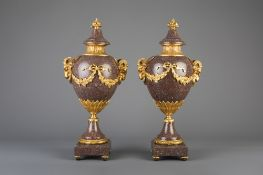 An imposing pair of gilt bronze mounted red porphyry cassolettes, 19th/20th C.