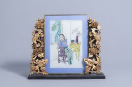 A Chinese painted glass window with a lady in an interior mounted in a wooden table screen, 19th/20t