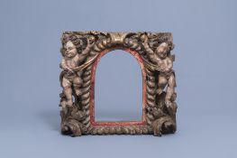 A carved and polychrome and gilt painted wooden tabernacle frame with putti, the Netherlands, 18th C