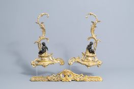 A pair of French Louis XV style patinated and gilt bronze andirons with putti, 19th C.