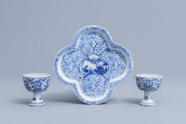 A pair of Chinese blue and white stem cups with floral design and a four-lobed teapot stand, Kangxi